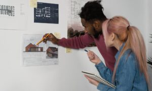 two people pointing at building blueprints on white wall